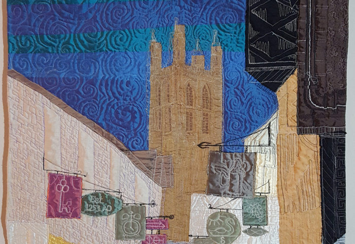 art quilt made of silks depicting Canterbury Cathedral in the background of a narrow lane lined with signs hanging from wrought iron posts, with three purple umbrellas in the foreground.